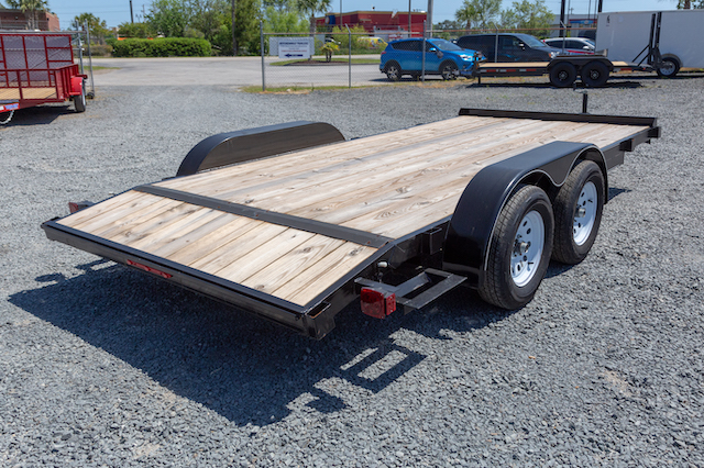 A open car hauler trailer with wood flooring is positioned in a gravel driveway.