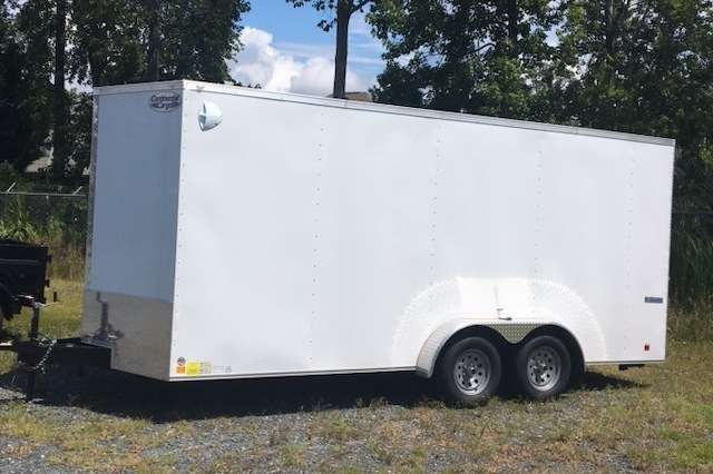 A photo of a white 7x18 Continental Cargo enclosed trailer outside in front of some trees.