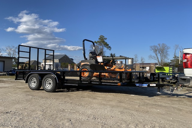 An orange zero-turn lawn mower in the bed of a 16' Top Hat Medium Pipe Utility Landscaping Trailer attached to a white pickup truck.