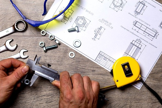 Close up of a person's hands using tools and blueprints