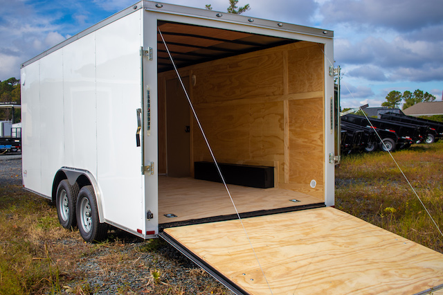 The back end of a white enclosed trailer with the back door ramp open.